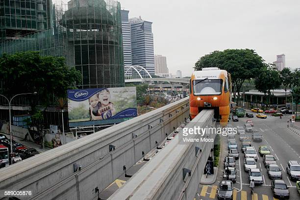 Passing congested traffic lines in every direction the monorail arrives at Bukit Bintang station in Kuala Lumpur's high end commercial center known...