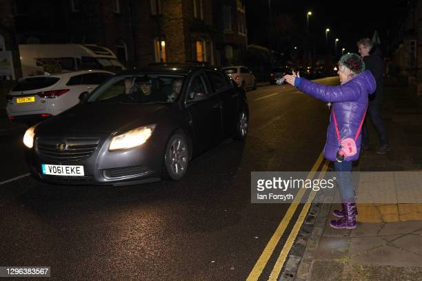 Passing motorist waves as a resident on a street in Saltburn stands outside her home and takes part in the Clap for Heroes event on January 14, 2021...