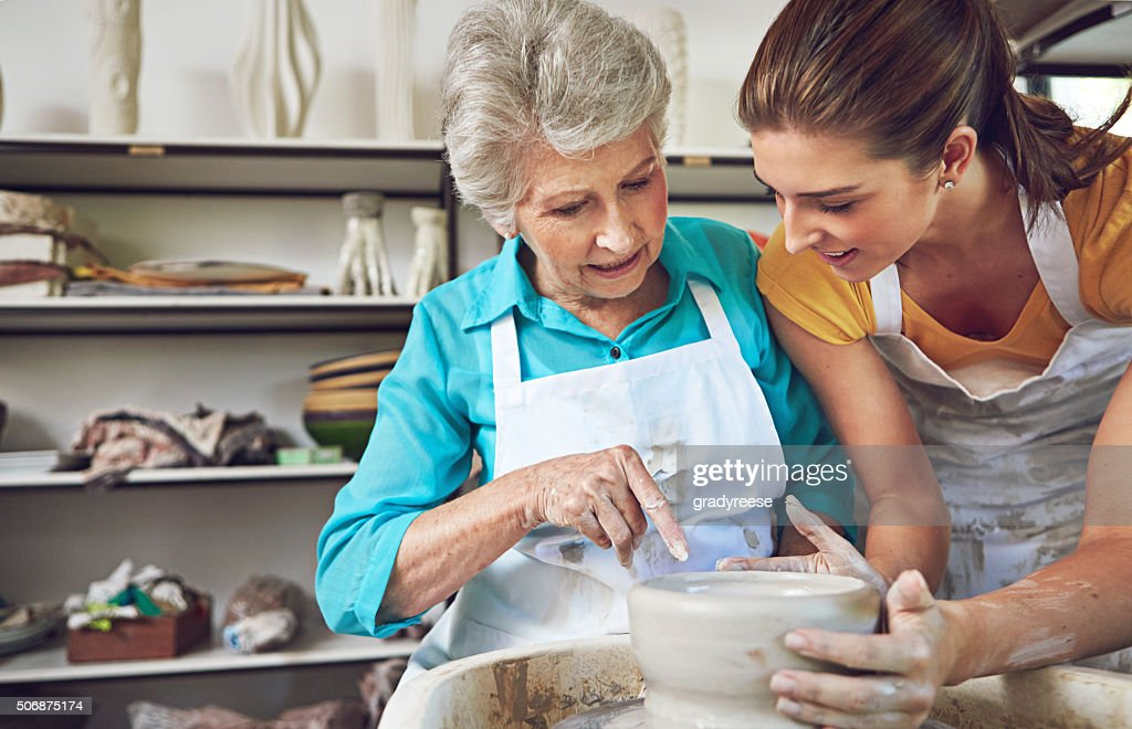 Passing on her pottery skills to Mom : Stock Photo