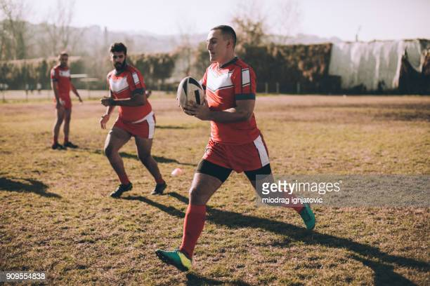 passing the ball on a rugby field - match sport stock pictures, royalty-free photos & images