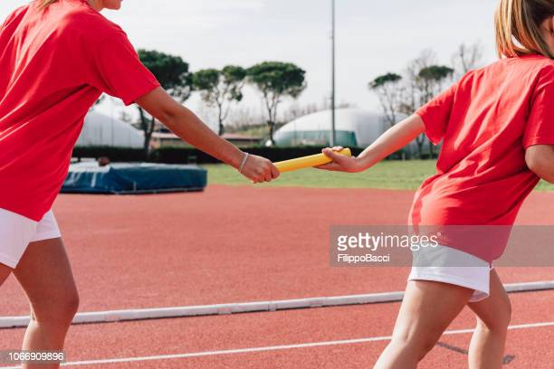 passing the relay baton on the track field - relay stock pictures, royalty-free photos & images