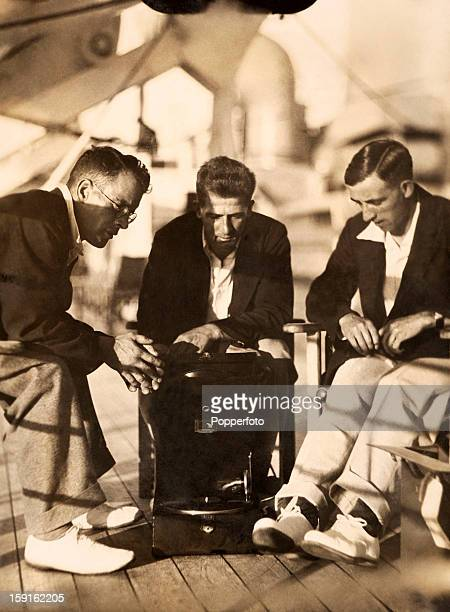 Passing the time during the long journey to Australia England cricketers Tom Mitchell Harold Larwood and Eddie Paynter listen to a gramophone on...