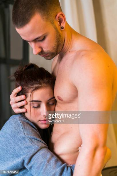 Passionate couple embracing at home