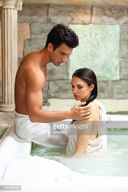passionate couple in hot tub at spa center - couple and kiss and bathroom stock photos and pictures