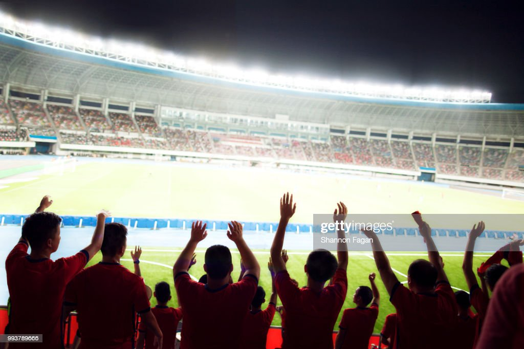 Passionate fans cheer and raise hands at a sporting event in the stadium : Stock Photo