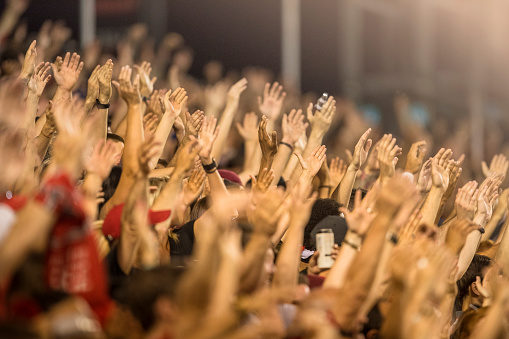 Passionate fans cheer and raise hands at a sporting event 937037584