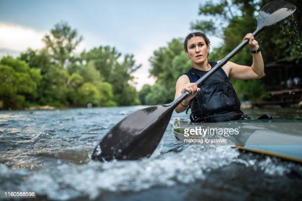 passionate female athlete in kayak - rafting stock pictures, royalty-free photos & images