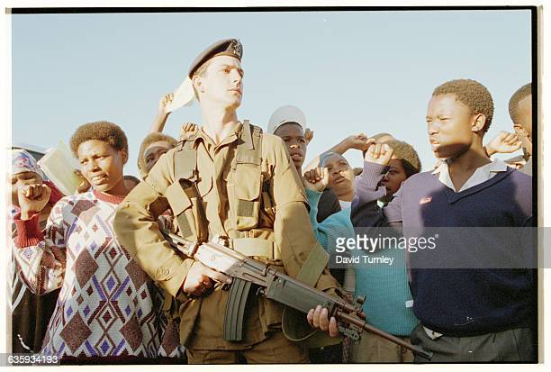 A passionate group of South Africans stand behind a military guard