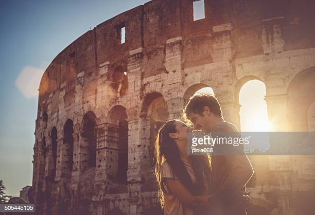 passionate kiss in front of the coliseum - coliseum rome stock photos and pictures