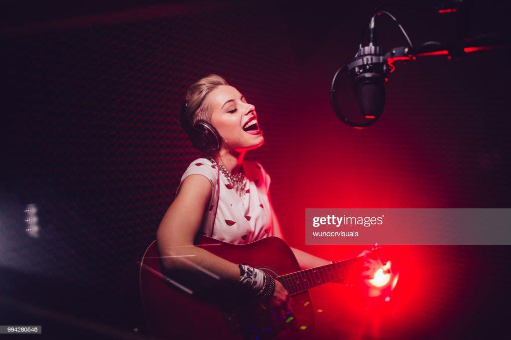 Apasionado cantante tocando la guitarra y grabar la canción en estudio : Foto de stock