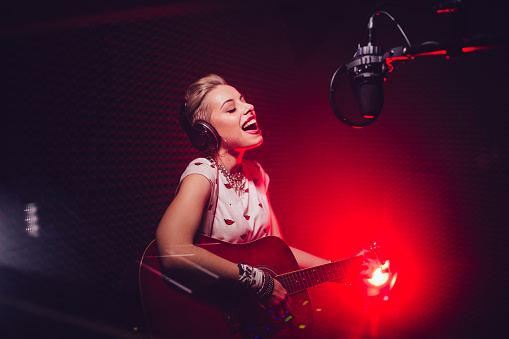 Passionate singer playing the guitar and recording song in studio 994280546