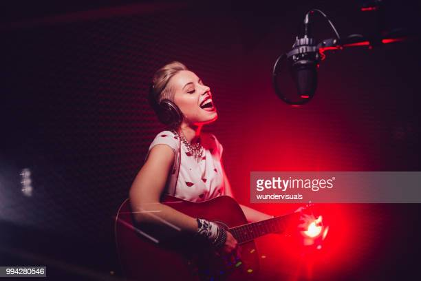 passionate singer playing the guitar and recording song in studio - cantare foto e immagini stock