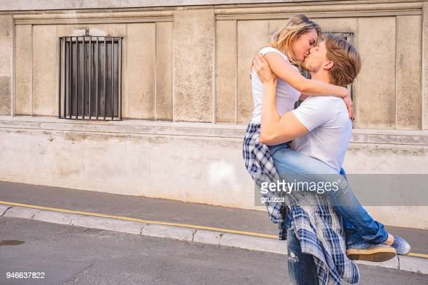Passionate young man and woman kissing and embracing on the city street