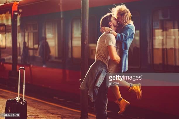 Leidenschaftlicher junger Mann und Frau, die neben den Zug am Bahnhof kissing