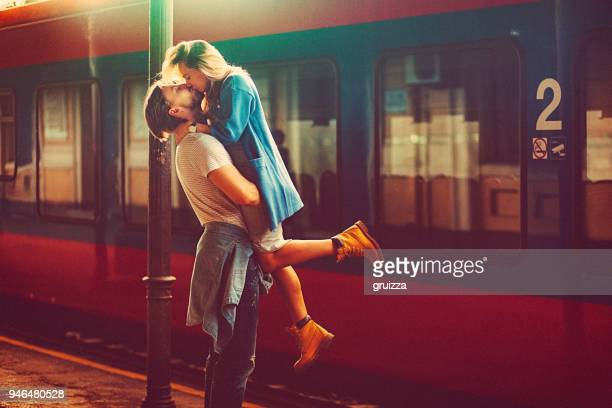passionate young man and woman kissing beside the train at the railway station - amor imagens e fotografias de stock