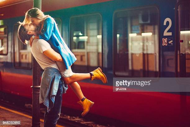 passionate young man and woman kissing beside the train at the railway station - coppia passione foto e immagini stock