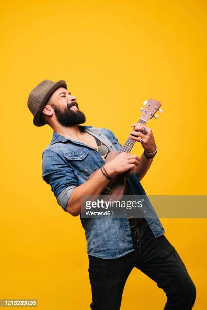 passionate young man in studio playing ukulele - musician photos et images de collection