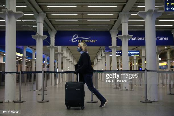 Passnger wearing a facemask arrives at the Eurostar terminal at St Pancras station in London on May 6, 2020 as life continues under a nationwide...