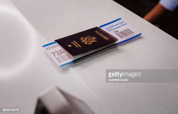passport and boarding pass on airline check-in desk at airport - security check stock photos and pictures
