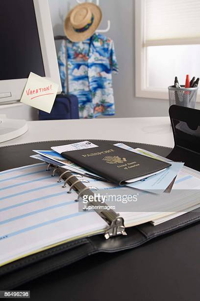 Passport and plane ticket on daily planner in office