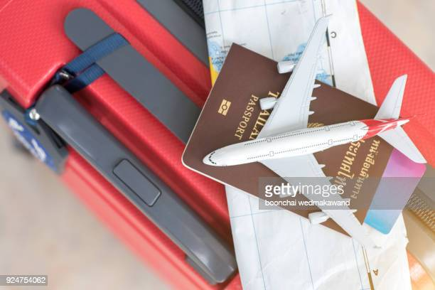 passport, boarding pass and toy airplane on luggage top view - passport stamp stock photos and pictures