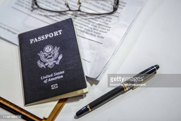 passport on the desk of an american businessman - passport stamp stock pictures, royalty-free photos & images