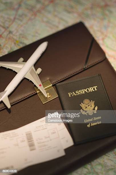 Passport , tickets , briefcase , toy plane , and road map