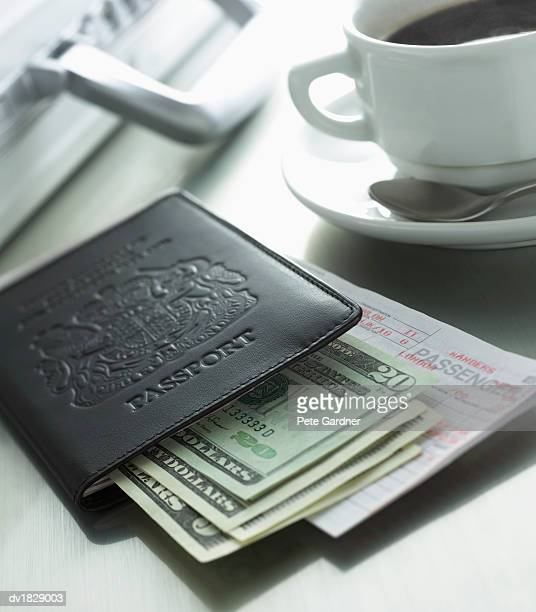 Passport, US Banknotes, Airplane Ticket on a Table