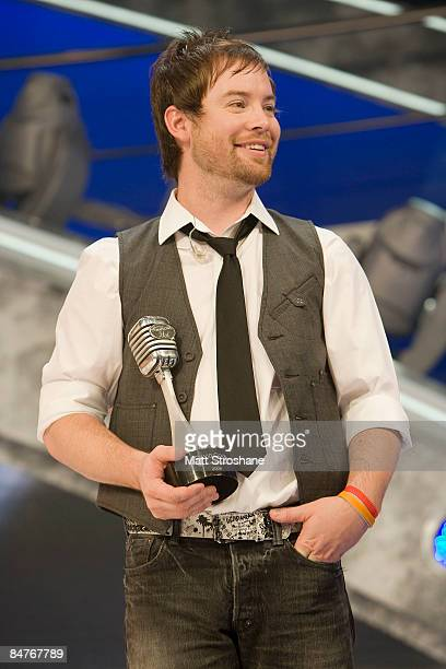 Past American Idol winners David Cook holds a microphone awards given to him by creator Simon Fuller after the grand opening show of the American...