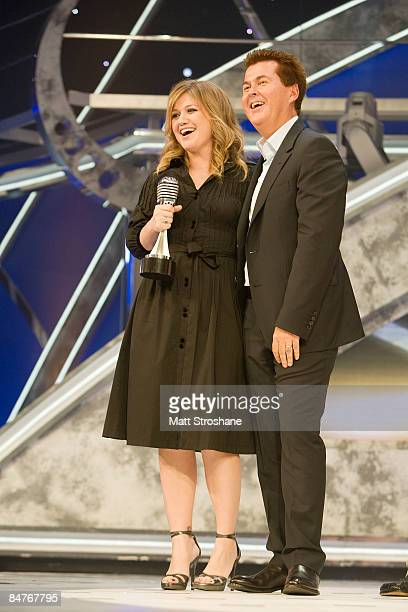 Past American Idol winners Kelly Clarkson holds a microphone awards given to him by creator Simon Fuller after the grand opening show of the American...