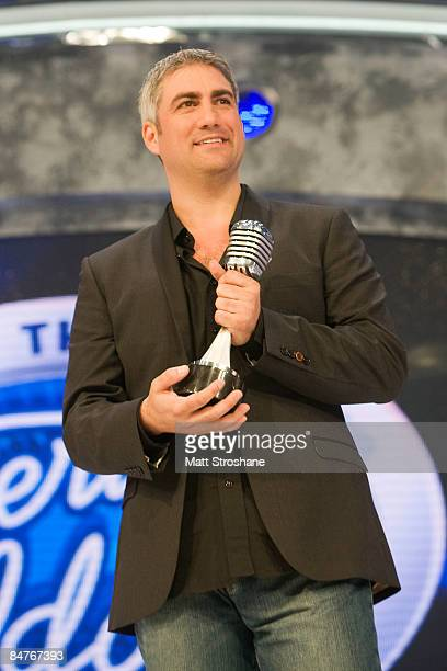 Past American Idol winners Taylor Hicks holds a microphone awards given to him by creator Simon Fuller after the grand opening show of the American...