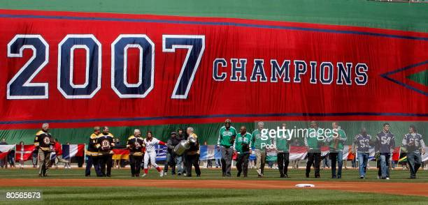 Past and present members of the NHL's Boston Bruins the NBA's Boston Celtics and the NFL's New England Patriots carry the Boston Red Sox' 2007 World...