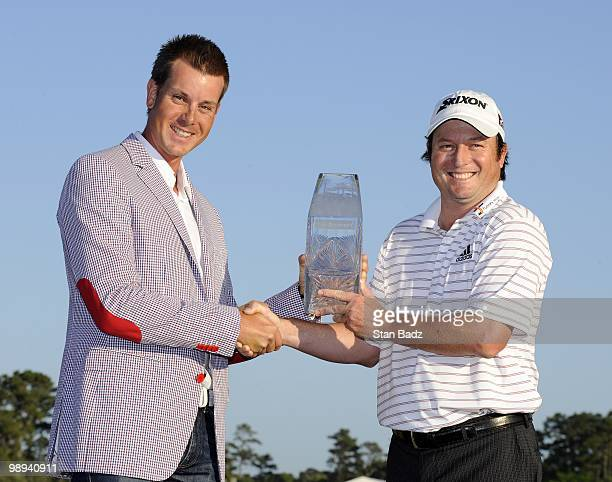 Past Champion Henrik Stenson presented Tim C lark with the winner's trophy after the final round of THE PLAYERS Championship on THE PLAYERS Stadium...