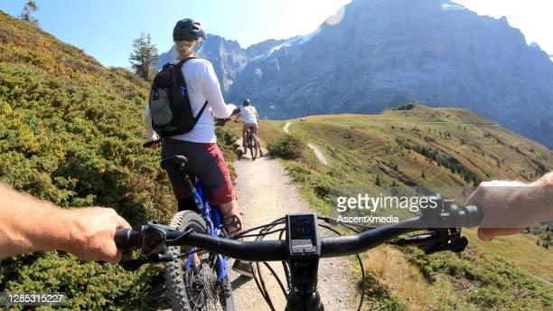 pov voorbij elektrische mountainbike aan rijpe vrouw en dochter mountainbiken - volgen activiteit stockfoto's en -beelden