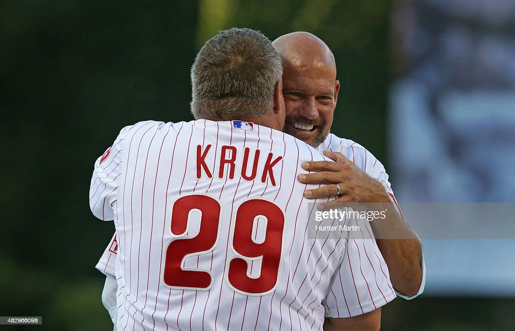 Past players Darren Daulton and John Kruk of the Philadelphia Phillies hug during the Pat Burrell 'Wall of Fame' Induction ceremony before a game against the Atlanta Braves at Citizens Bank Park on July 31, 2015 in Philadelphia, Pennsylvania. The Phillies won 9-3.