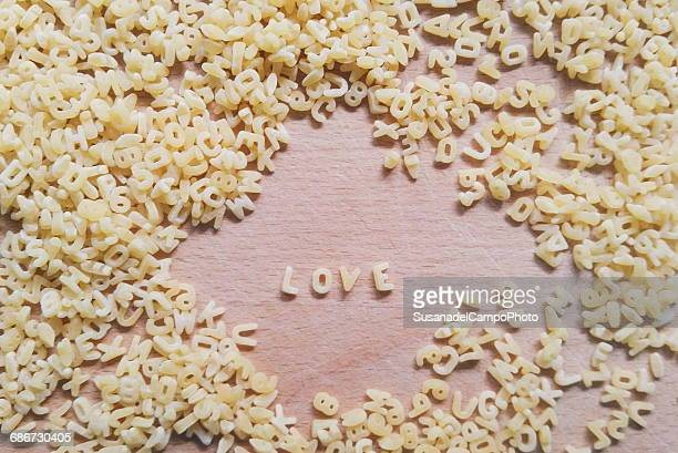 pasta alphabet capital letters spelling the word love - capital letter stock pictures, royalty-free photos & images
