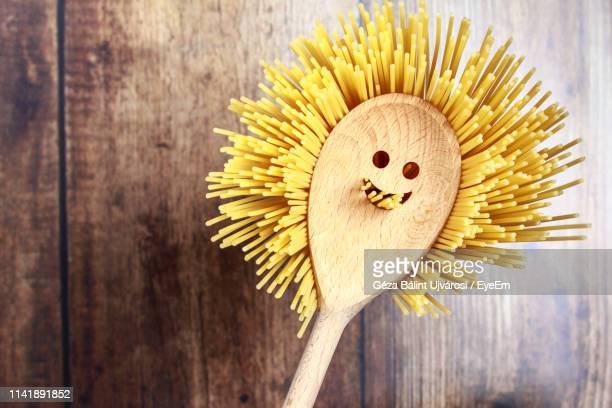 pasta and anthropomorphic face pattern spoon on table - anthropomorphic smiley face stock pictures, royalty-free photos & images