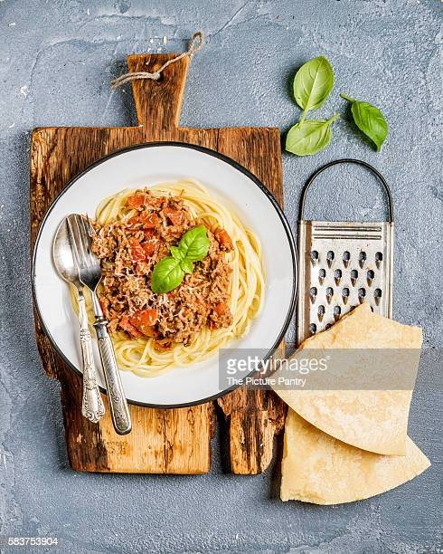 Pasta dinner. Spaghetti Bolognese in metal plate on rustic wooden board with Parmesan cheese, grater and fresh basil over grey concrete background