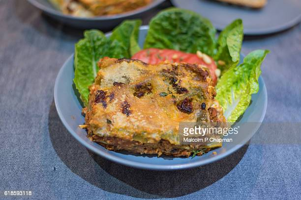 Pasta dish - Lasagne Verdi served on a plate with tomatoes and lettuce.