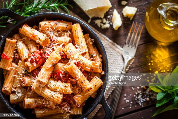 Pasta in a cast iron pan shot from above on rustic wooden table