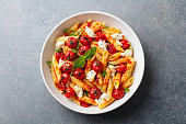 Pasta penne with roasted tomato, sauce, mozzarella cheese. Grey stone background. Top view.