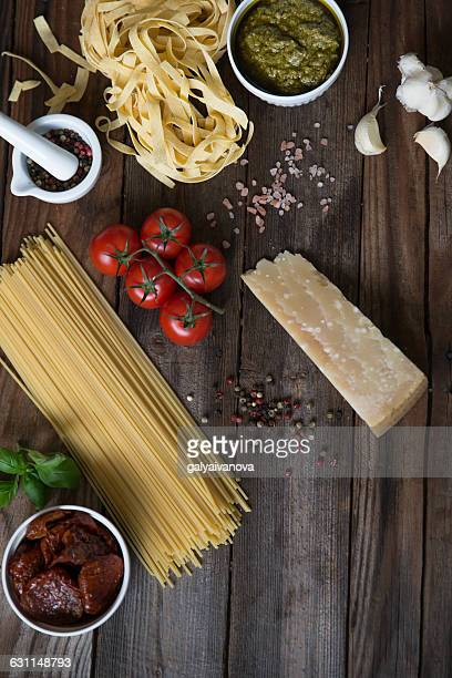 Pasta, pesto, garlic, tomatoes and parmesan on table