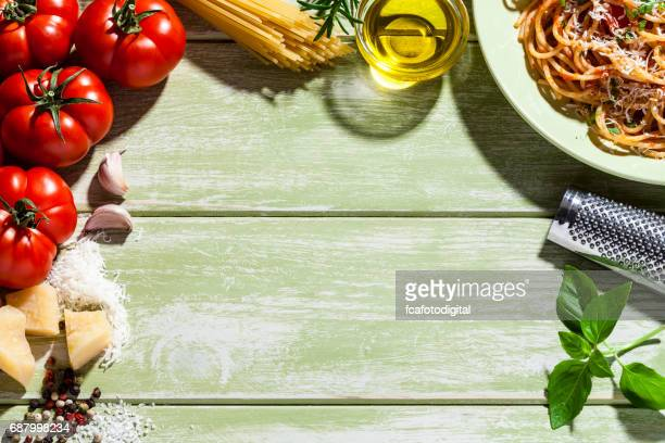 Pasta plate and ingredients frame on green kitchen table