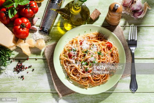 pasta plate and ingredients on green kitchen table - garlic clove imagens e fotografias de stock