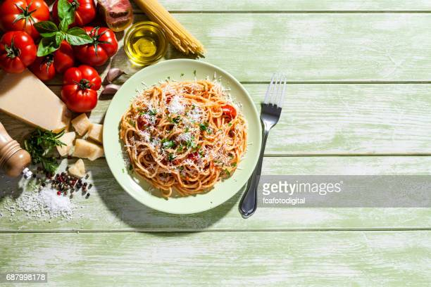 Pasta plate and ingredients on green kitchen table