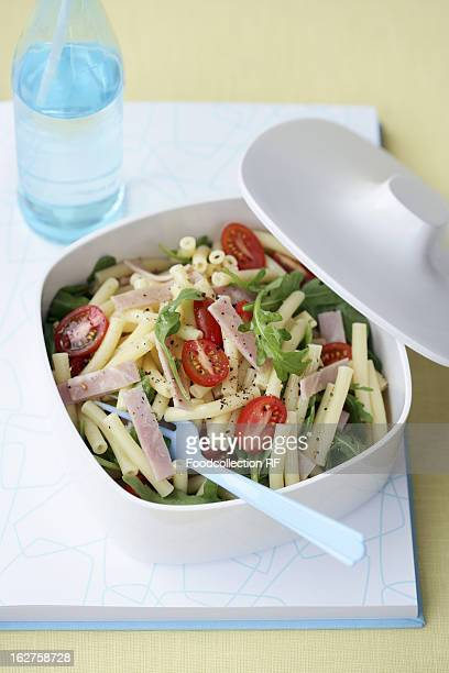 Pasta salad with ham, rocket and tomatoes in plastic box