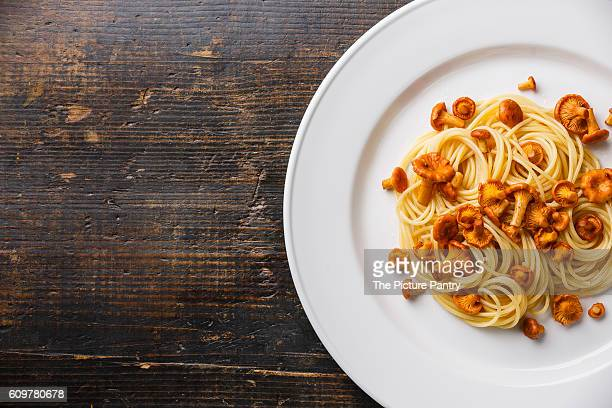 Pasta spaghetti with wild forest mushrooms chanterelle on white plate and copy space background
