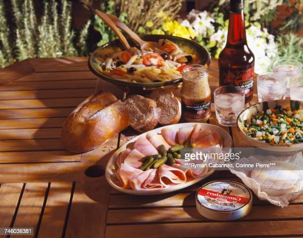 Pasta ,tomato and olive salad,boiled ham and cheese on a table outdoors