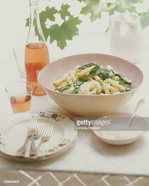 Pasta with basil in a bowl and rose wine.