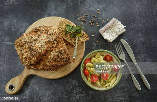 pasta with cherry tomatoes and parsley with brown bread and pesto - bowl stock pictures, royalty-free photos & images